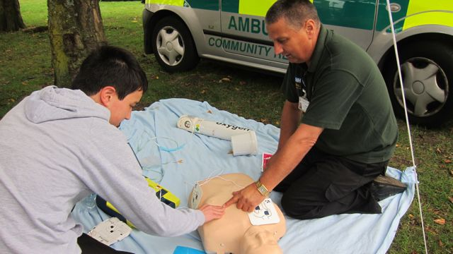 Malcolm Wing teaches my son Ben how to use the defibrillator.