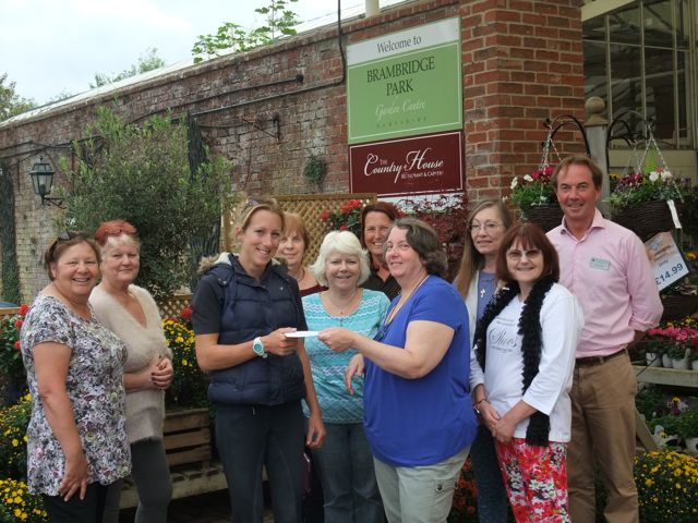Mrs Sue Potter (in blue) from Brambridge Craft Club presented £350 to Flick from Riding for All.