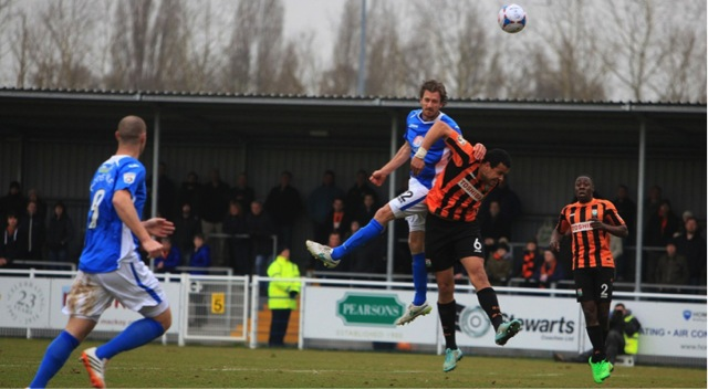 Eastleigh Jack Midson outjumps the Barnet defender but his header goes wide.