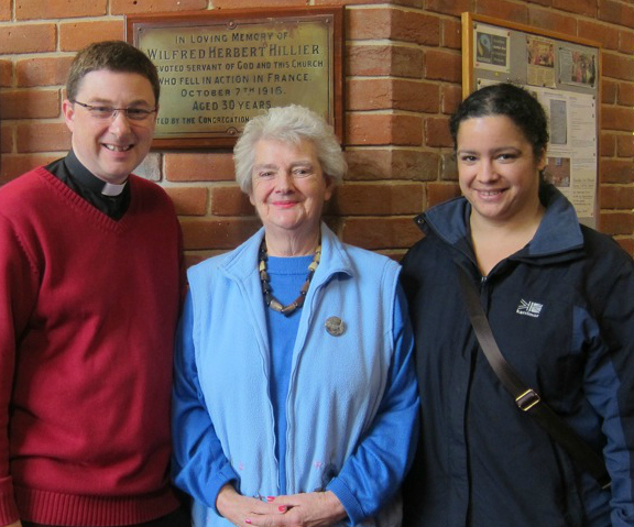 Reverend Peter Cornick, Barbara Hillier, and her daughter Jo Nash in front of the plaque which remembers  Barbara's great uncle Wilfred Herbert Hillier.