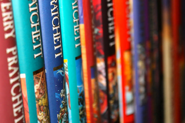 "Books by Sir Terry Pratchett. Image by <a href=""https://www.flickr.com/photos/daviddmuir/16103517907"">David Muir</a> via Flickr."