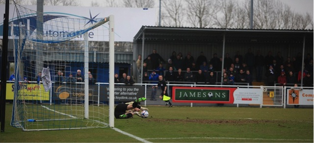The Barnet keeper saves down to his left.