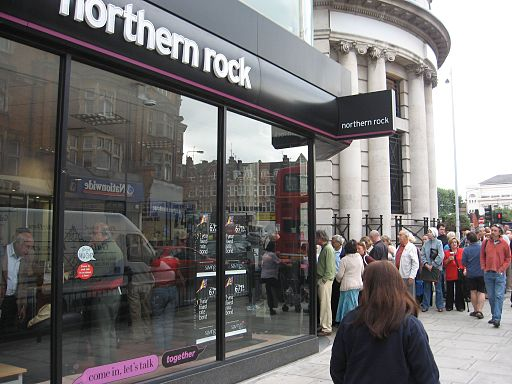 Customers queueing to retrieve their savings saving from Northern Rock during the banking collapse in 2007. By Alex Gunningham from London, Perfidious Albion (UK plc) (Northern Rock Customers, Golders Green.) [CC BY 2.0 (http://creativecommons.org/licenses/by/2.0)], via Wikimedia Commons