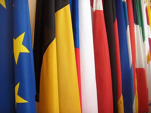 "Flags of the European Union Members. Image by <a href=""https://www.flickr.com/photos/friendly-fire/33431056/in/photolist-3XkTw-49JB98-q3T2W-85rYyr-6KnpEc-7y3GEX-9uhLp9-6KnrKT-b7T2L-bsm26R-Cv5sq6-ho25ZF-8DUxMY-9WmVKM-dPGiAB-518NwF-8DRyoZ-8DRw3i-vQ7Wjw-51o7Up-8ofXhv-bAHRgU-8s4uTN-ojL9NK-RecwG-8n25hm-9oevVo-sAFtQK-ojtwiP-sjeGg8-512Qvp-5ea3NH-sAFEQR-anXcK-4Wd2aK-nsMZeV-6KFk4A-cMm5dC-3JBMkQ-6NaYnK-98jRi8-2hDzyp-2hJ16L-6uNLxh-dmN9fy-7xumha-8ofWzD-7gK9og-Gg4WS-53fkaP"">tristam sparks</a> via Flickr."
