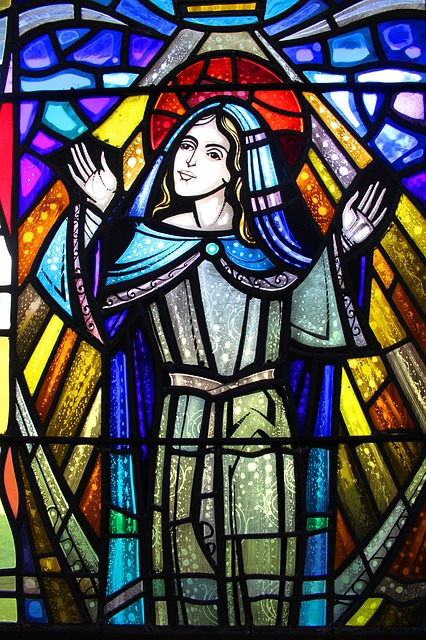 Stained glass window. A happy looking saint. Pixabay image