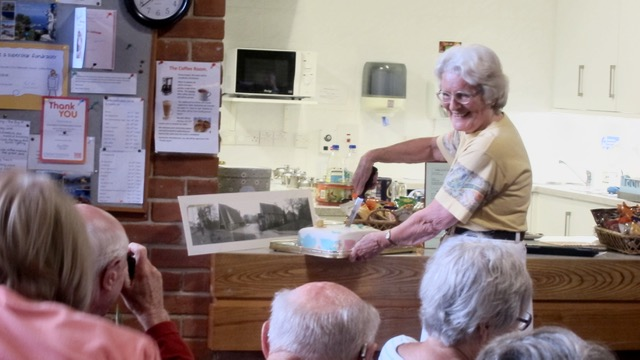 Jane cutting the cake. Next to it is a photograph of the Methodist Church before Dovetail Centre was built.