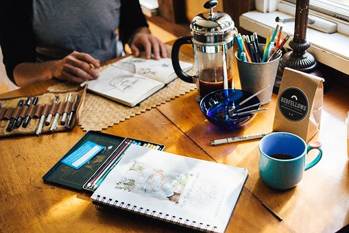 Notebooks, beverages and pens - bliss for any writer - image via Pixabay
