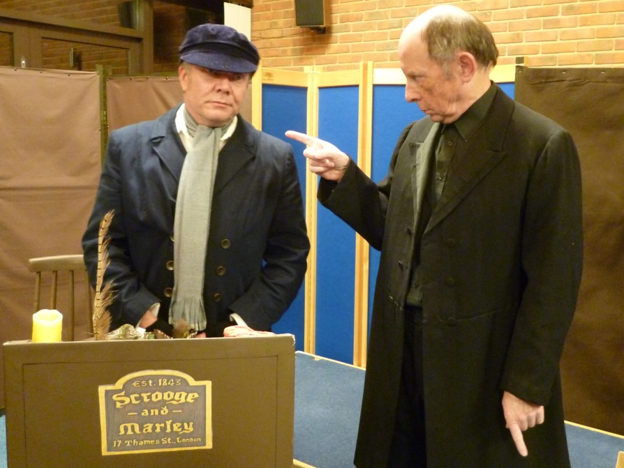 Bob Cratchit (Mike Slatcher) is berated by Ebenezer Scrooge (Lester Parry)