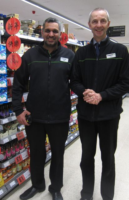 Sonny with shop manager David in front of Chinese New Year food.