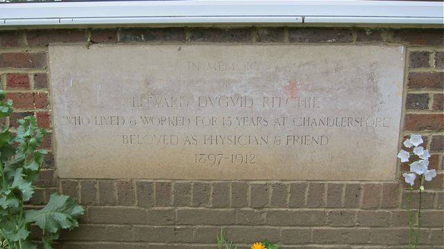 "The plaque in memory of Mr Edward Dvgvid Ritchie on the outside wall of the Ritchie Memorial Hall, Hursley Road, Chandler's Ford. ""who lived and worked for 15 years at Chandlersford, beloved as physician & friend. 1897 – 1912."""