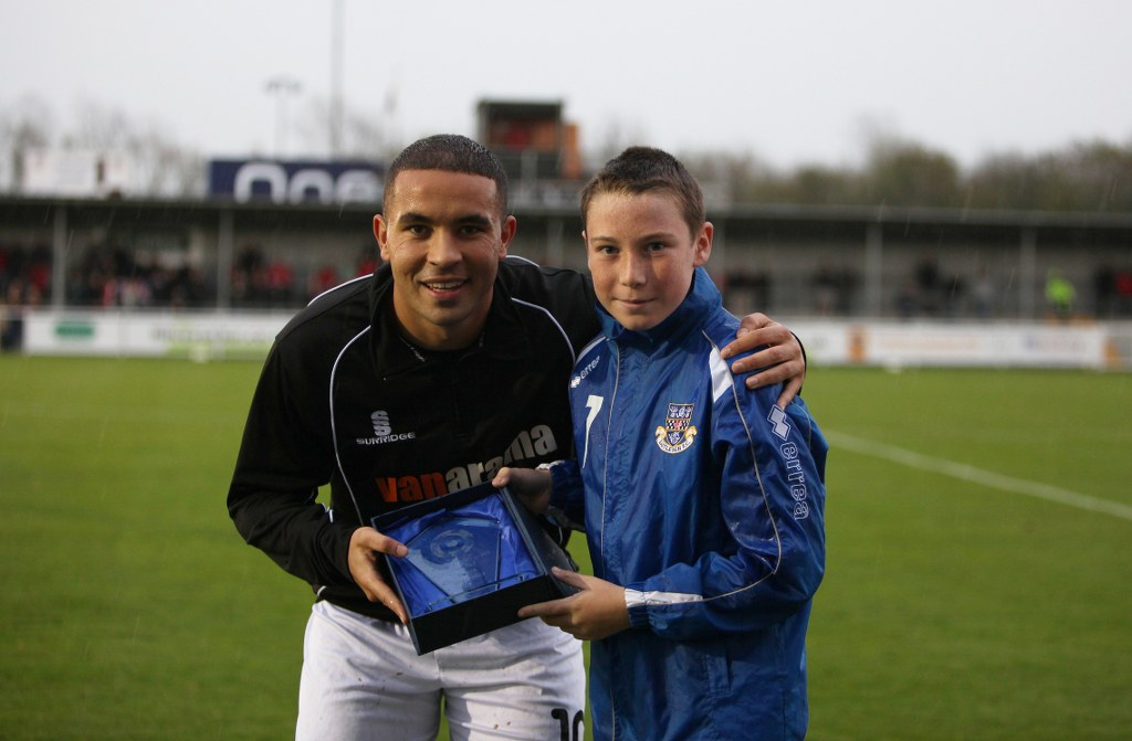 October player of the month Jai Reason receives his award from young Eastleigh player Josh Hoey before the game.