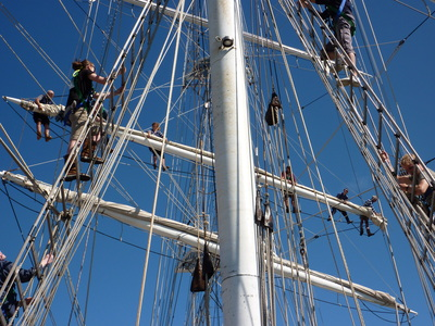 The rigging comes alive as crew climb to release the sails.