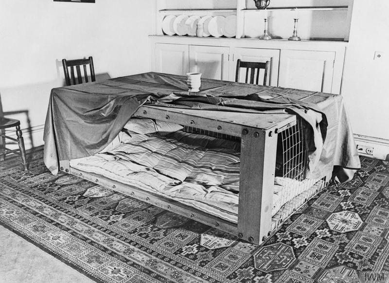 A photograph of a Morrison shelter in a room setting, showing how such a shelter could be used as a table during the day and as a bed at night. © IWM (D 2053)
