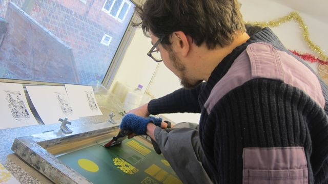 "<a href=""http://bru-ha.com/"">Andrew Reaney</a> shows a child how to screen print a Christmas card."