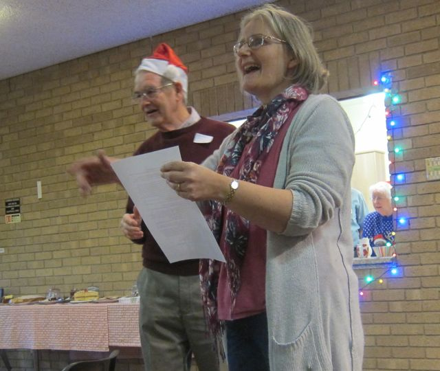 Judith Bird revealed the Christmas Quiz answers. (Left: volunteer Jim Rooke)