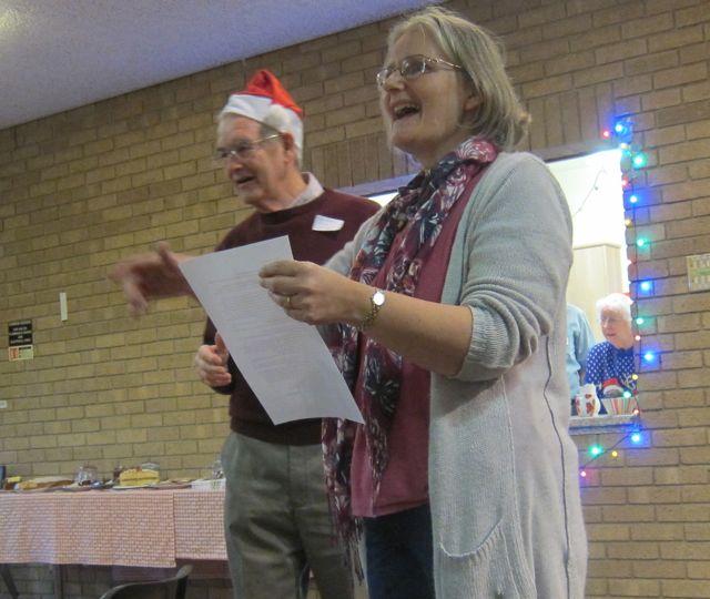 Judith Bird revealed the Christmas Quiz answers. (Left: volunteer Jim Rooke)