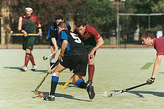 Hockey on a modern all weather pitch. Number 5 is using his stick reversed