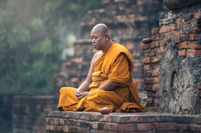 A monk's sitting quietly. Image via Pixabay