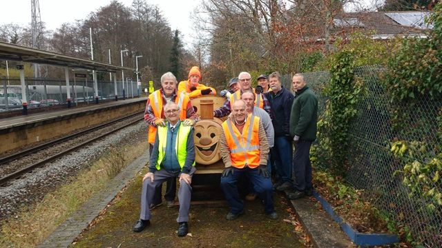 Eastleigh Men's Shed members with the smiley train planter, at the disused platform of Chandler's Ford Station.