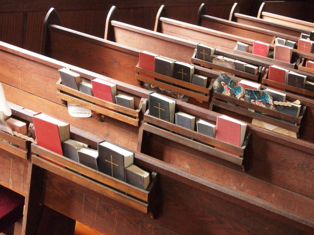 Many hymn books crammed into the book shelves