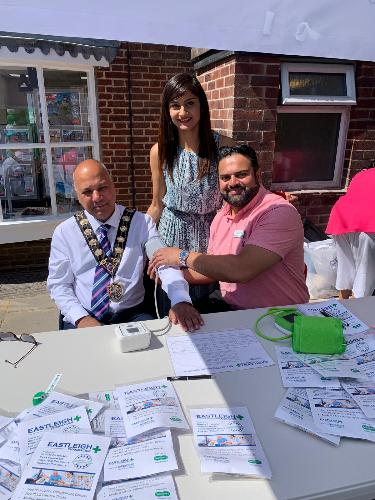 Optician Minal (centre) runs the new Specsavers in Chandler's Ford. Her cousin pharmacist Mitesh Patel checks the blood pressure of Eastleigh Mayor.