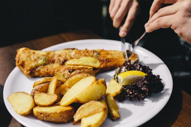 kaboompics_Dinner at reastaurant Fish and Roasted Potatoes with Fresh Greek Salad