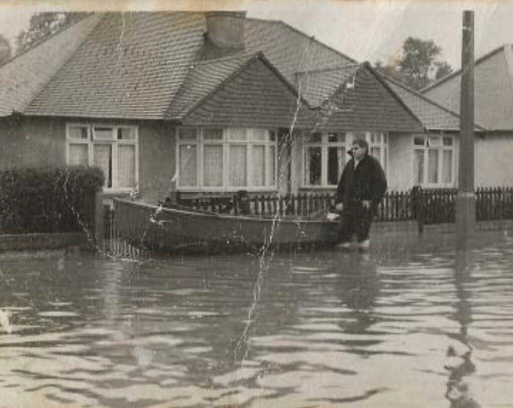 Peter Aged 18 holding firemans boat waiting to rescue people from flooded bungalows in Chandler's Ford.